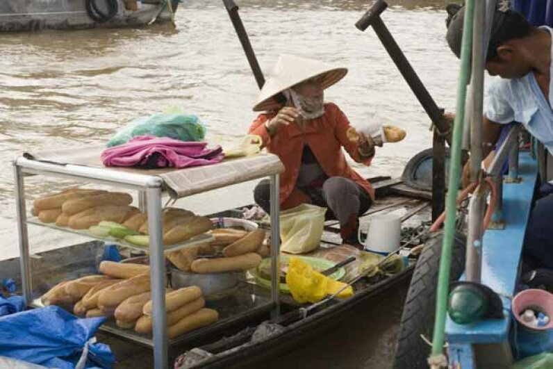 A banh mi vendor plies her wares from a boat in Vietnam. Jupiterimages/Photolibrary/Getty Images