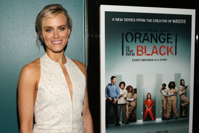 "Taylor Schilling, aka Piper Chapman on ""Orange Is the New Black,"" poses next to a promotional poster. Jesse Grant/Getty Images for Netflix"