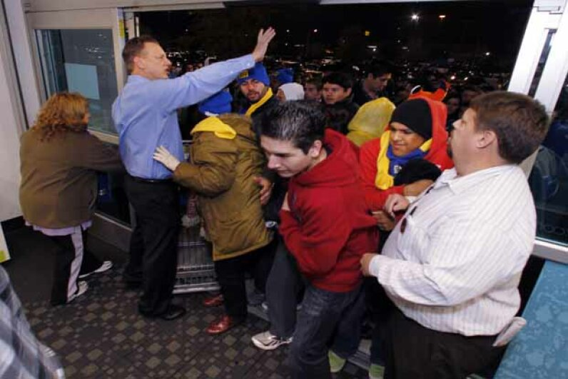 Best Buy general manager Terry Dilts (left) and assistant manager Robert Knowles (right) try to control the crowd at the front door to the Mesquite, Texas store. © David Woo/Dallas Morning News/Corbis