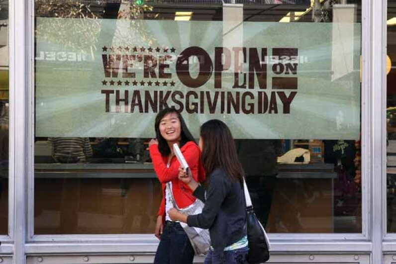 Pedestrians walk by an advertisement for Thanksgiving Day hours at an Old Navy store in San Francisco. Justin Sullivan/Getty Images