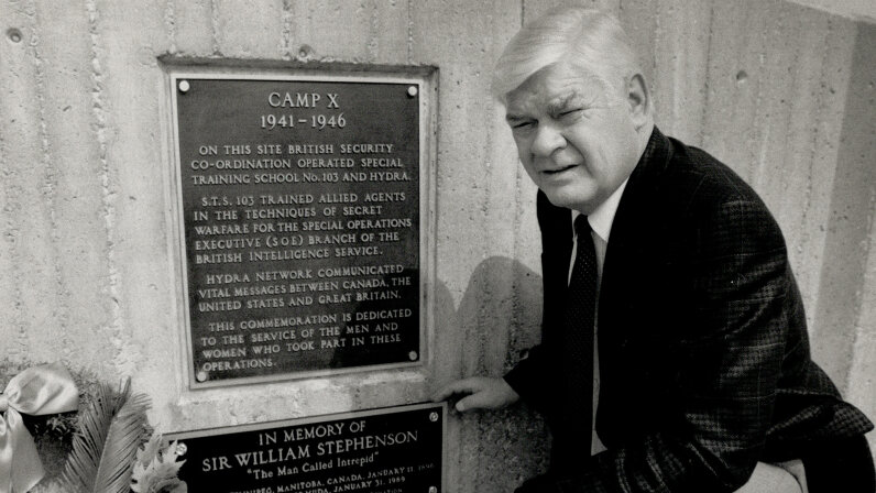 Former Whitby, Ontario, Mayor Bob Attersley kneels next to a Camp X plaque. It was top secret in its heyday, but Camp X is now recognized as a notable historical site. Paul Irish/Toronto Star via Getty Images