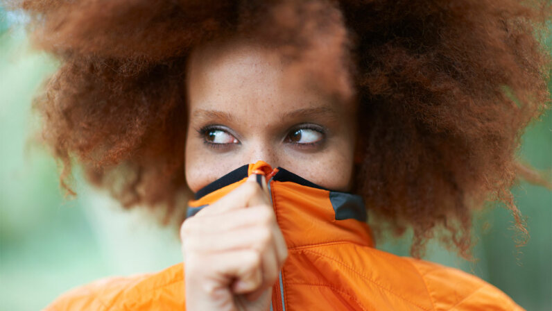 woman with orange sweater pulled over mouth