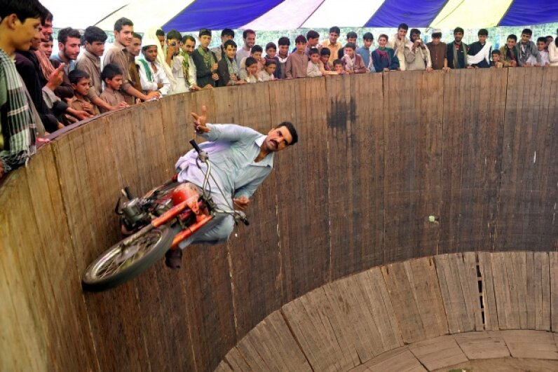 As if riding a motorcycle on a wall weren't risky enough, this bold performer decided to take his hands off the handles.  Noorullah Shirzada/AFP/Getty Images