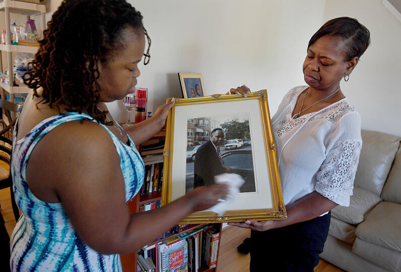 Lawanda Fearrington (left) and her sister Nicole both have familial dilated cardiomyopathy, a heart condition that killed their father in 2003 (shown in the picture they are looking at). Their other two sisters have the same illness. Michael S. Williamson/The Washington Post via Getty Images