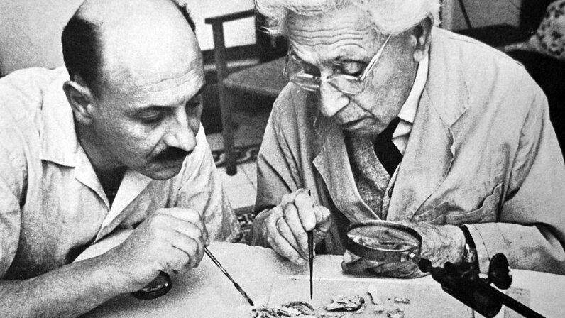 Archaeologist Yigael Yadin (left) and Israeli professor James Biberkraut study samples from the Dead Sea Scrolls in 1965. Universal History Archive/UIG via Getty images