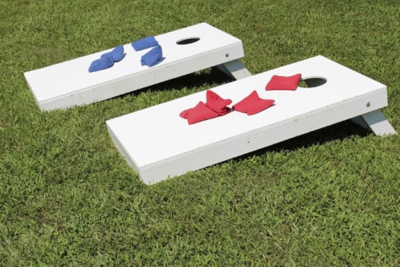 Cornhole -- also known as corn toss or bean bag toss -- takes up little space and can be played while still holding your plate of cake. ©iStockphoto.com/SarahPage