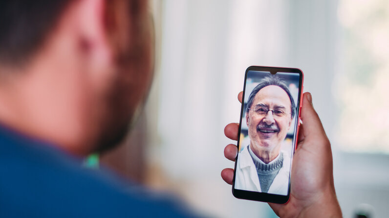 Patient at home talking to a doctor online through a mobile phone