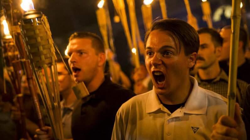 """Peter Cvjetanovic (R) along with neo-Nazis, """"alt-right,"""" and white supremacists encircle and chant at counter protesters at the base of a statue of Thomas Jefferson after marching through the University of Virginia campus with torches in Charlottesville, Virginia, on Aug. 11, 2017.  Samuel Corum/Anadolu Agency/Getty Images"""