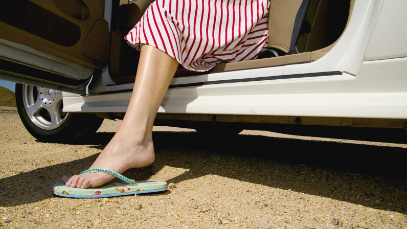Woman wearing flip-flops stepping out of a car