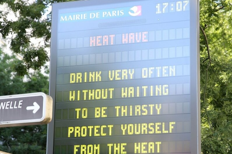 A sign in Paris in summer 2015 warns tourists of heat danger. © Pierre Suu/Getty Images