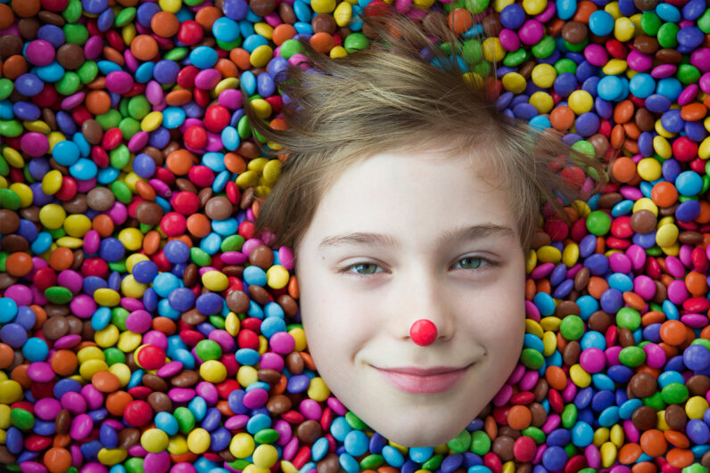 A child in a pile of multicolor candies