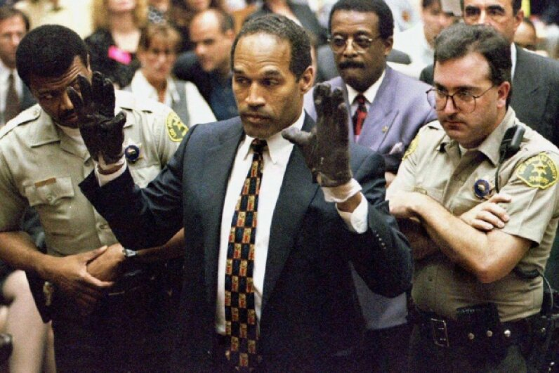 O.J. Simpson tries on the gloves found at the crime scene and his home before the jury and the court on June 15, 1995. ©SAM MIRCOVICH/X90064/Reuters/Corbis