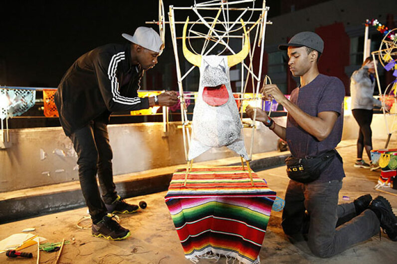 """Darius (left) and Cameron (right) of """"The Amazing Race"""" must build the frame of a 'torito,' a paper mache bull rigged with fireworks, hoist it to the top of a 15-foot pole and light it. Competition shows are not usually rigged because of strict federal laws. Robert Voets/CBS via Getty Images"""