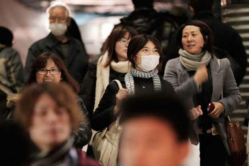 Commuters in Tokyo wear surgical masks to help protect themselves from an influenza outbreak. Adam Pretty/Getty Images