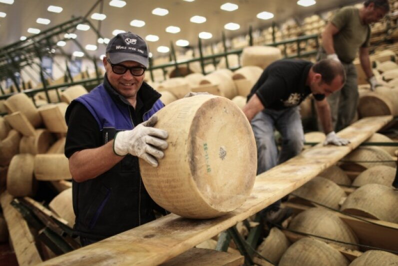 A man moves a wheel of Parmigiano-Reggiano at the Coopertiva Cappelletta, which produces the famous cheese. © Federico Scoppa/Demotix/Corbis