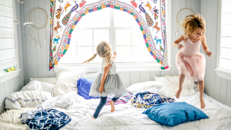 girls jumping on bed
