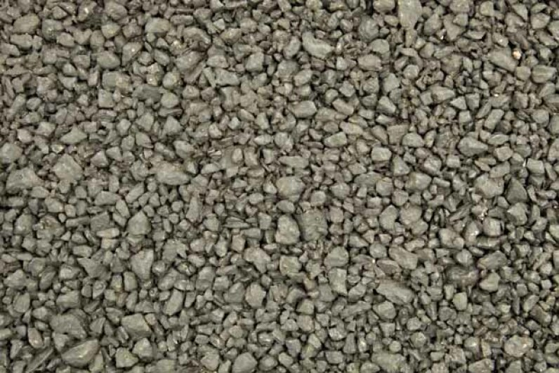 The larger aggregate and lack of sand in pervious asphalt (shown here) creates interconnected voids, allowing water to flow through the surface rather than off it, which reduces stormwater runoff. BanksPhotos/E+/Getty Images