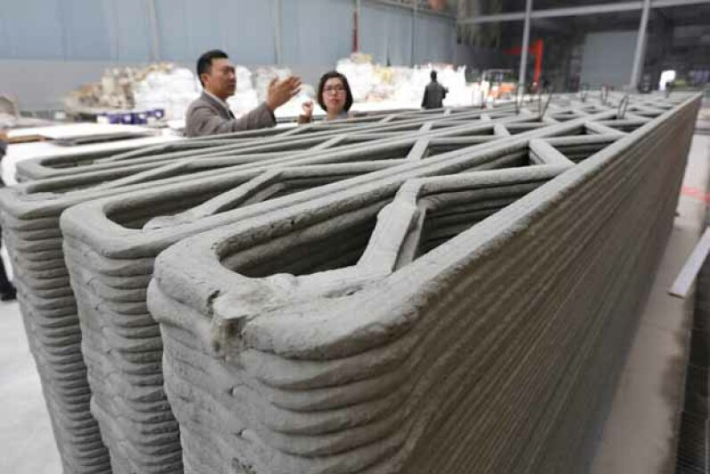 Ma Yihe (left) shows the 3D-printed walls for houses his company is building in Shanghai, China. His company plans to build 10 of these in a day. © Pei Xin/Xinhua Press/Corbis