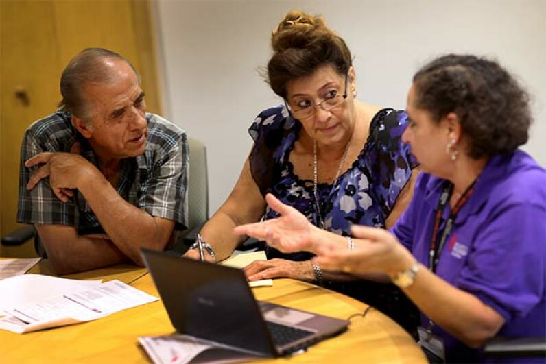 Affordable Care Act navigator Nini Hadwen (R) speaks with Jorge Hernandez (L) and Marta Aguirre as they shop for health insurance during a navigation session put on by the Epilepsy Foundation Florida. Joe Raedle/Getty Images