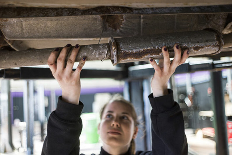 A woman mechanic fixes a car exhaust pipe at an innovative garage and auto repair workshop catering exclusively to female customers in Paris, 2014. Customers can get a massage or manicure while they wait. FRED DUFOUR/AFP/Getty Images