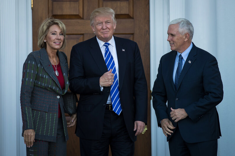 Betsy DeVos, President Donald Trump's pick for Secretary of Education, poses for a photo with Trump and Vice President Mike Pence.