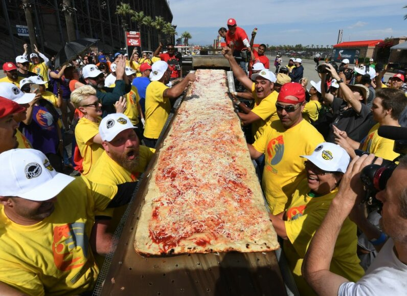 "Volunteers feed the final section of the pizza into the mobile oven as they successfully break the Guinness World Records title for ""Longest Pizza"" with a length of 1.32 miles (2.13 kilometers) at the Auto Club Speedway track, in Fontana, California on June 10, 2017.  MARK RALSTON/AFP/Getty Images"
