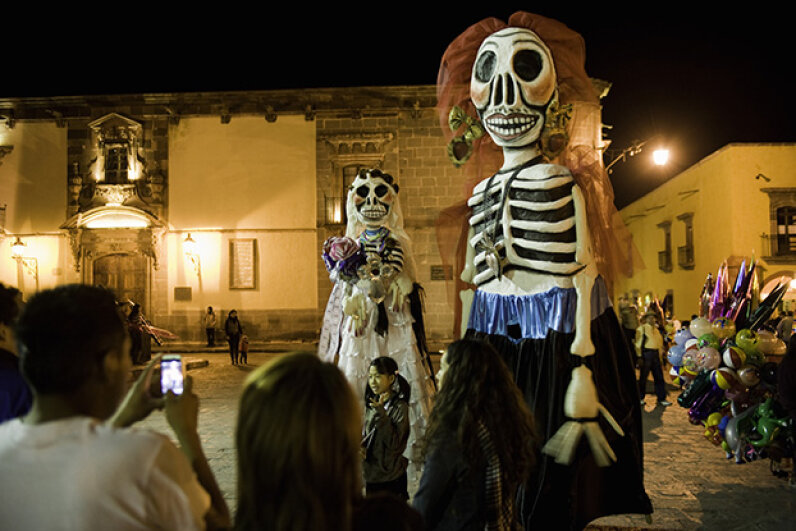 A parade in honor of El Dia de los Muertos passes through a town in Mexico. This is a major holiday in the country. Darryl Leniuk/Photographer's Choice/Getty Images