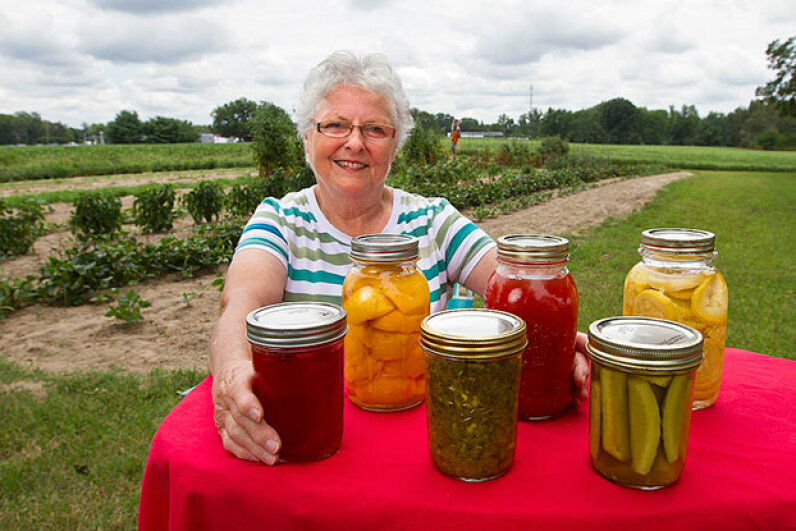 Susiette Jackson poses near her garden with some of the canned goods that she's planning to enter at the state fair. Dill pickles are front right. Norm Shafer/for the Washington Post/Getty Images