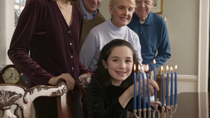 Little girl lighting menorah