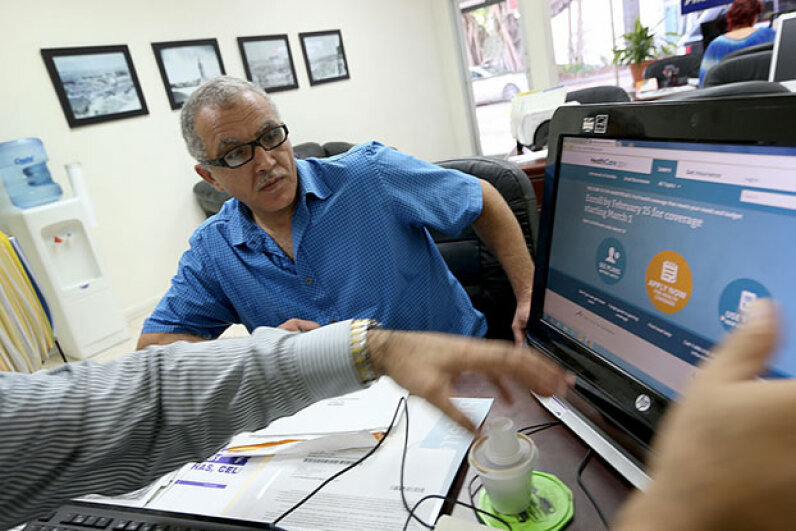 Hisham Uadadeh enrolls in a health insurance plan under the Affordable Care Act with the help of A. Michael Khoury at Leading Insurance Agency in Miami. Joe Raedle/Getty Images