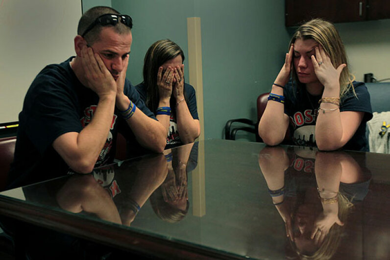Family members of Boston Marathon bomb victim and subsequent amputee Marc Fucarile are devastated after Dr. Jeremy Goverman talks to them. Many U.S. families are doubly traumatized, first by a patient's illness and then by the enormous medical bills. Bill Greene/The Boston Globe via Getty Images