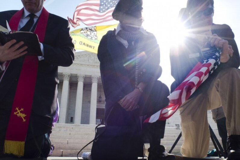 Demonstrators pray outside the U.S. Supreme Court on day three of oral arguments over the constitutionality of the Patient Protection and Affordable Care Act on March 28, 2012. © MLADEN ANTONOV/AFP/Getty Images