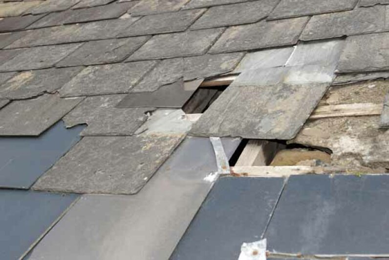 Inspect your roof twice a year for missing shingles, tears and other damage. morrbyte/iStock/Thinkstock