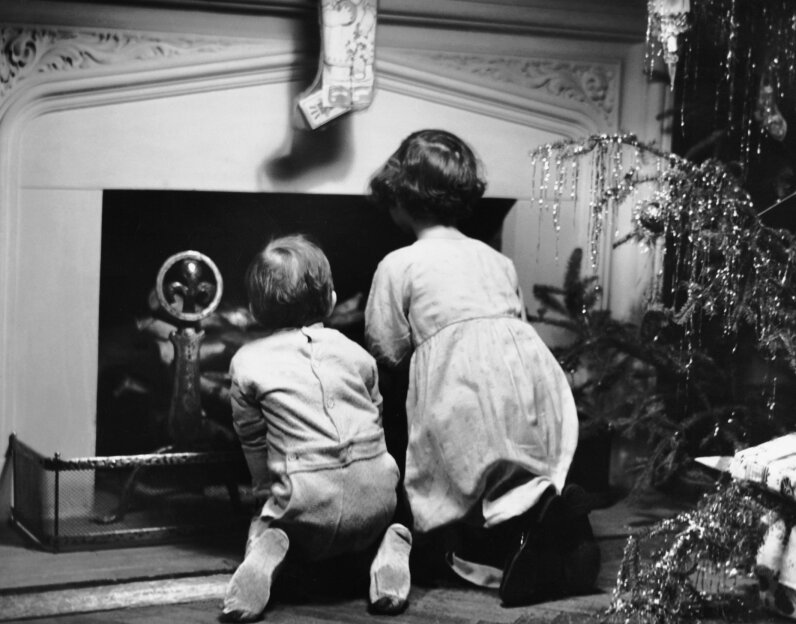 Two kids wait for Santa to come down the chimney, circa 1950s. Some people think teaching children to believe in Santa undermines parents' credibility. George Marks/Retrofile/Getty Images