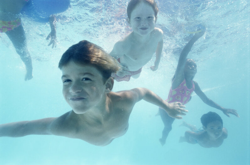 Children swim underwater.