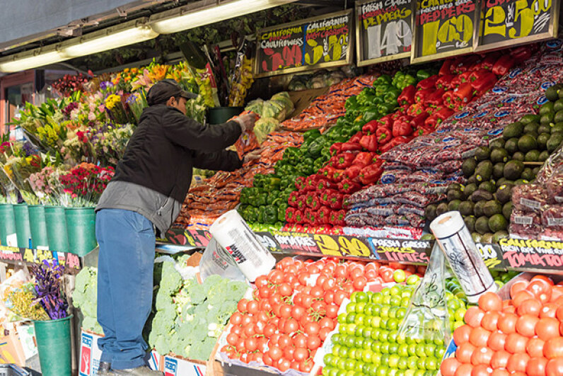 A Mexican immigrant arranges fruit in a convenience store in New York City. One study showed immigrants bettered the earnings of native-born Americans. Roberto Machado Noa/LightRocket via Getty Images