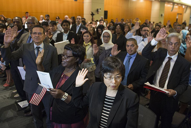 People take the U.S. citizenship oath during a naturalization ceremony at the U.S. Patent and Trademark Office in Alexandria, Virginia, May 28, 2015. SAUL LOEB/AFP/Getty Images