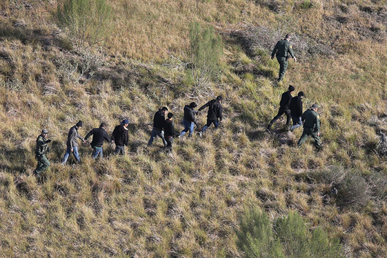 U.S. Border Patrol agents lead undocumented immigrants out the brush after capturing them near the U.S.-Mexico border at La Grulla, Texas. While a large number of unauthorized immigrants are nabbed at this border, not all of them are from Mexico. John Moore/Getty Image
