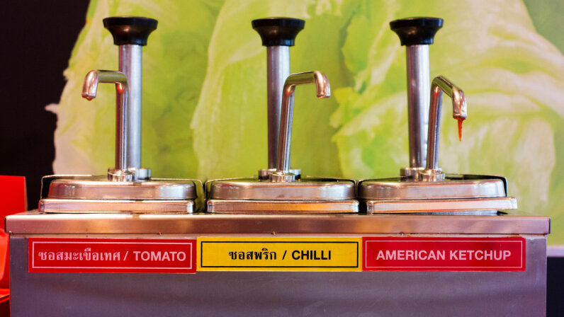 A product labelled 'American ketchup' sits next to two local condiments in a fast food restaurant in Thailand. Peter Ptschelinzew/Lonely Planet/Getty Images