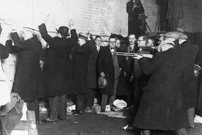 This re-enactment of the St. Valentine's Day Massacre shows the members of Al Capone's gang pretending to be policemen and lining up George Moran's men against the wall to kill them. © Bettmann/CORBIS