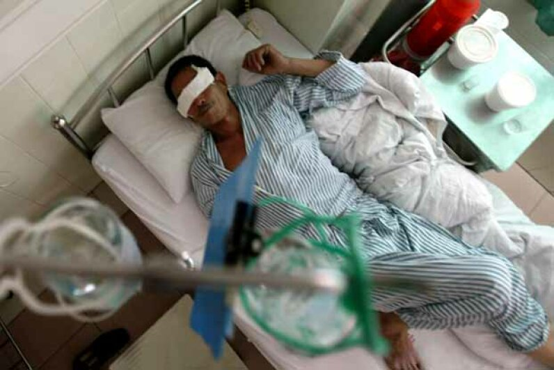 A victim of some poisoned moonshine lies in a hospital in China. © CHINA PHOTOS/Reuters/Corbis