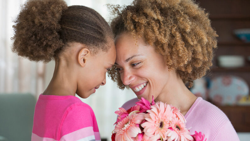 mother getting flowers from her little girl