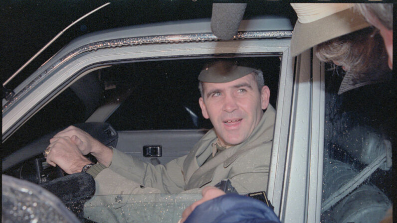 Marine Lt. Col. Oliver North leaves his home early on Dec. 18, 1986,  in suburban McLean, Virginia. North, the fired National Security Council member, was under fire for his reported role in the Iran arms-Contra aid controversy.  Bettmann/Getty Images