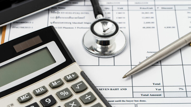 medical bills, stethoscope, calculator