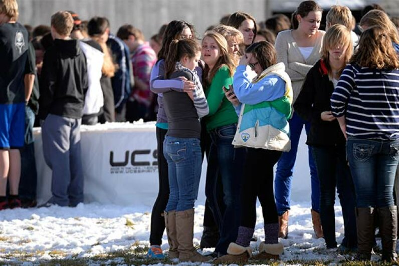 Students comfort each other as they stand on the football field after a gunman was spotted inside Arapahoe High School, Colorado on Dec. 13, 2013. John Leyba/The Denver Post via Getty Images