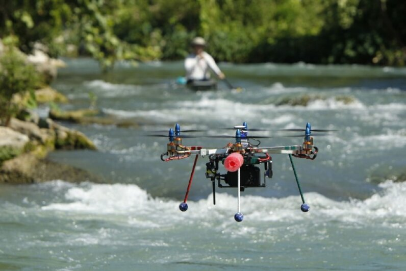 A UAV with a camera mounted on it photographs a canoe race on the San Marcos River in Martindale, Texas June 6, 2012. © Erich Schlegel/Corbis