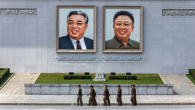Soldiers walk in front of giant portraits of Kim Il Sung (L) and Kim Jung Il on Kim Il Sung square, Pyongyang, North Korea. Cappronnier Benoit/Getty Images
