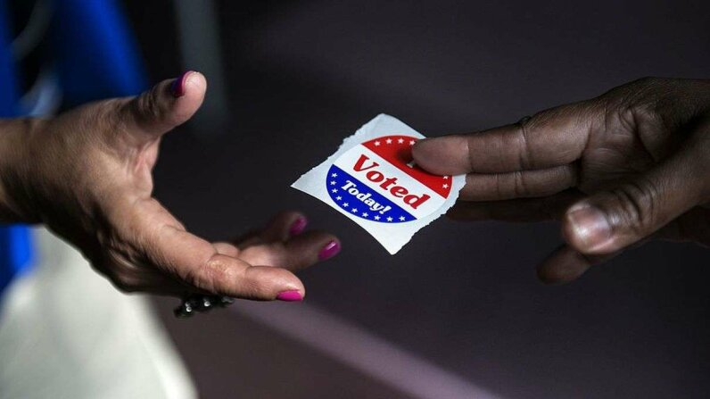 A poll worker hands out 'I Voted Today' stickers during the first day of early voting October 22, 2012 in Washington, D.C. BRENDAN SMIALOWSKI/AFP/Getty Images