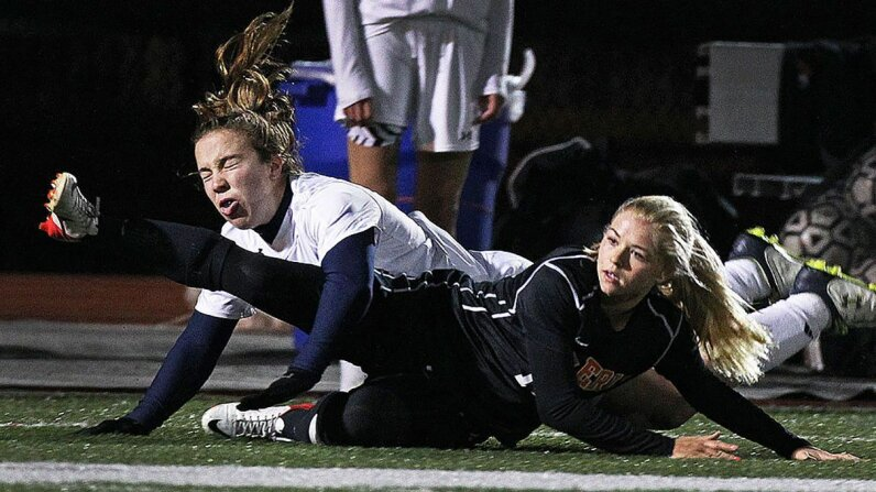 Two high-school soccer players collide in a play for control of the ball. Jim Davis/The Boston Globe/Getty Images