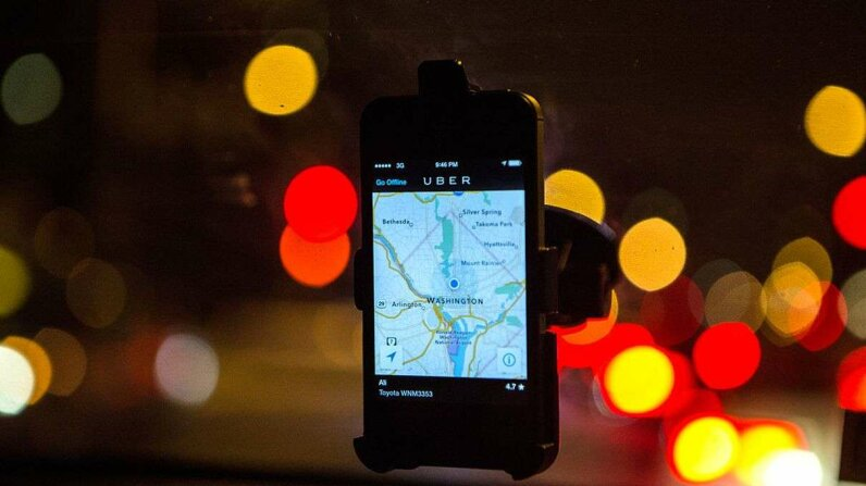 The Uber driver app is displayed on the windshield of Uber driver Ali Jaghori. Evelyn Hockstein/For The Washington Post via Getty Images